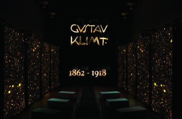 Nello schermo centrale la famosissima firma di Gustav Klimt cui cui l'artista era solito segnare le sue opere