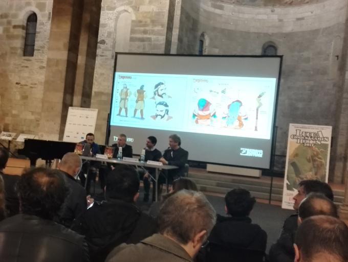 Stefano Vietti, Luca Barbieri e Luca Enoch presentano il mondo espanso di Dragonero, mentre alle loro spalle scorrono alcuni studi per i personaggi della serie Dragonero Adventures.