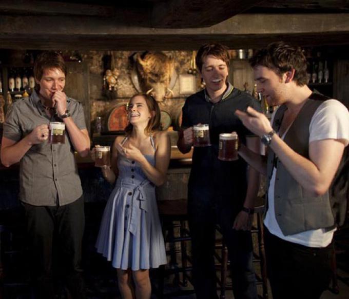 Emma Watson (Hermione), i gemelli Phelps (Fred e George) e Matthew Lewis (Neville), dismessi gli abiti potteriani, sorseggiano una Burrobirra
