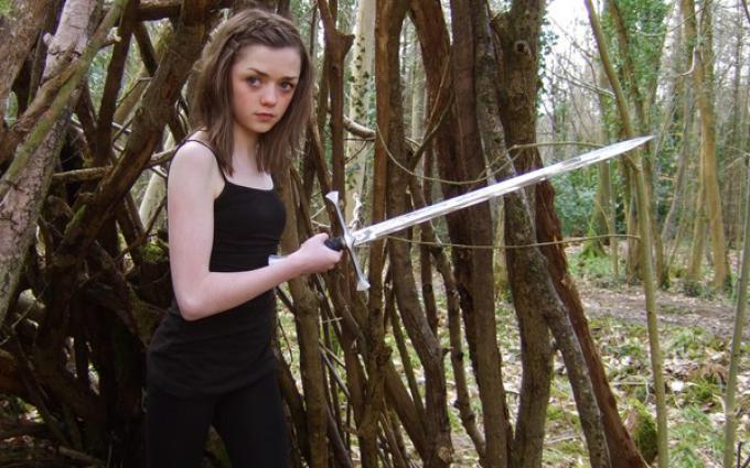 Maisie Williams alias Arya Stark brandisce Ago in Game of Thrones.