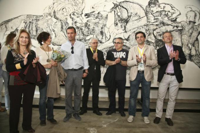 Il murale alle spalle del sindaco è del famosissimo fumettista scomparso nell'88 Pazienza. Murale che Paz realizzo' nell'87 e che ora e' stato completamente recuperato ed esposto al pubblico in occasione di Napoli Comicon alla presenza del direttore Claud