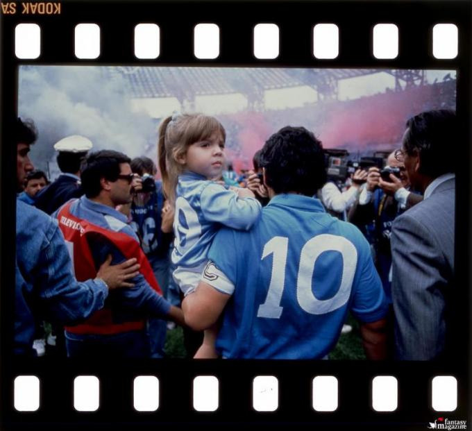 Diego Maradona enters the pitch holding his daughter Dalma, on the day of Napoli's second 'scudetto'.  Photo by Renato Carbone.